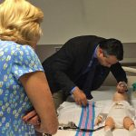Kiran Hebbar, M.D. demonstrates the mechanical (simulator) infant for Marcia Taylor and Taylor Family Foundation members as they tour the facility.